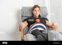 Pregnant woman lying in lounge chair with an apple on her ...