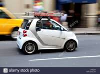 A white Smart Car with roof rack and step ladder Stock
