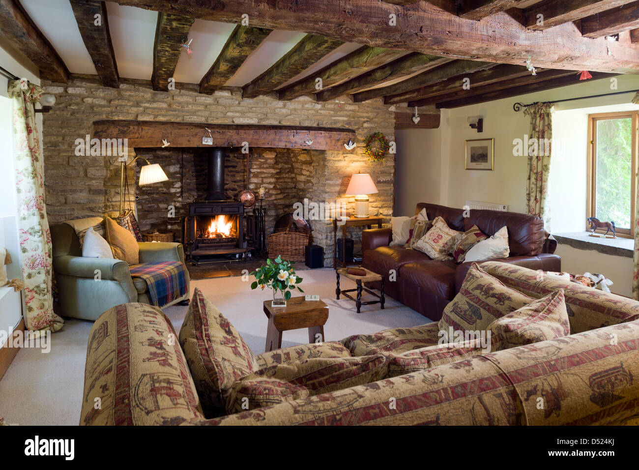 cosy living room with log burner pottery barn chairs a cottage burning stove exposed stone walls and ceiling beams features