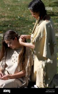 A Native American Indian woman braiding the hair of a ...