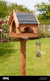 Wooden bird table with slate roof and a seed feeder in a ...