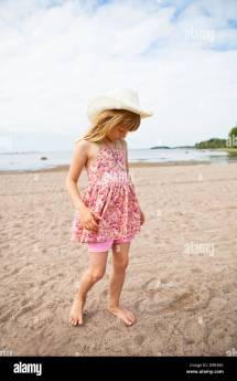 Thoughtful Young Barefoot Girl Wearing Hat And Pink