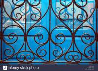 Decorative iron ironwork window grates on wood shuttered