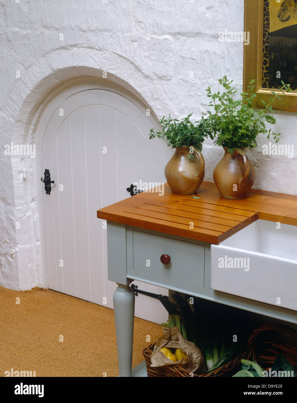 kitchen draining board white hutches for herbs in pottery jugs on wooden freestanding stock unit with belfast sink next to original arched doorway