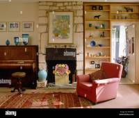 Pink armchair and open wall shelves in country living room