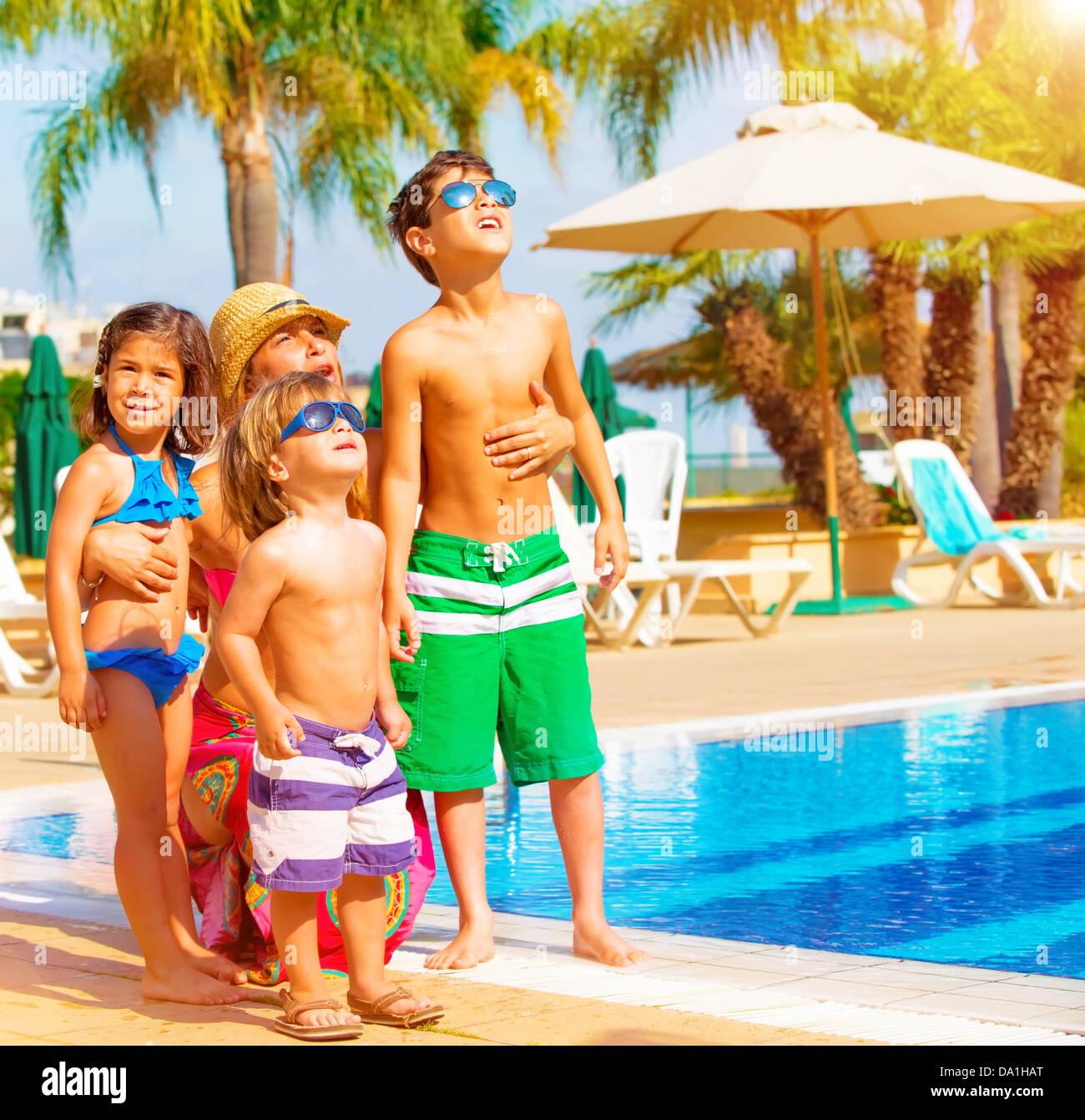 Cute happy family having fun near pool on luxury tropical resort Stock Photo Royalty Free Image