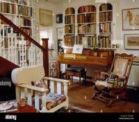 Antique spinet below fitted bookcase in cottage living ...