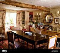 Upholstered chairs at antique oak table in cottage dining ...