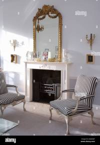 Antique gilt mirror above white fireplace in living room ...