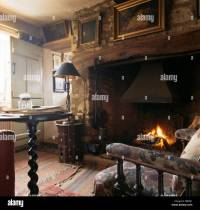Pictures on wall above inglenook fireplace in old ...