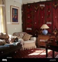 Old red Persian carpet hanging on wall in townhouse living