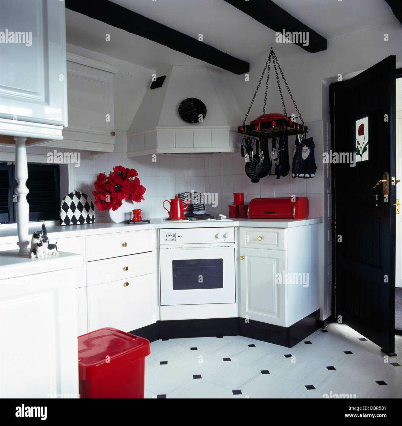 Red accessories in black and white kitchen with black