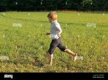 Young Barefoot Boy Running Grass