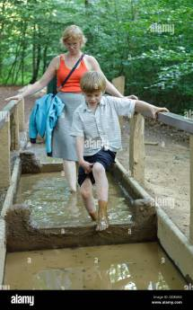 Mother And Son Walking Pool Of Mud Barefoot