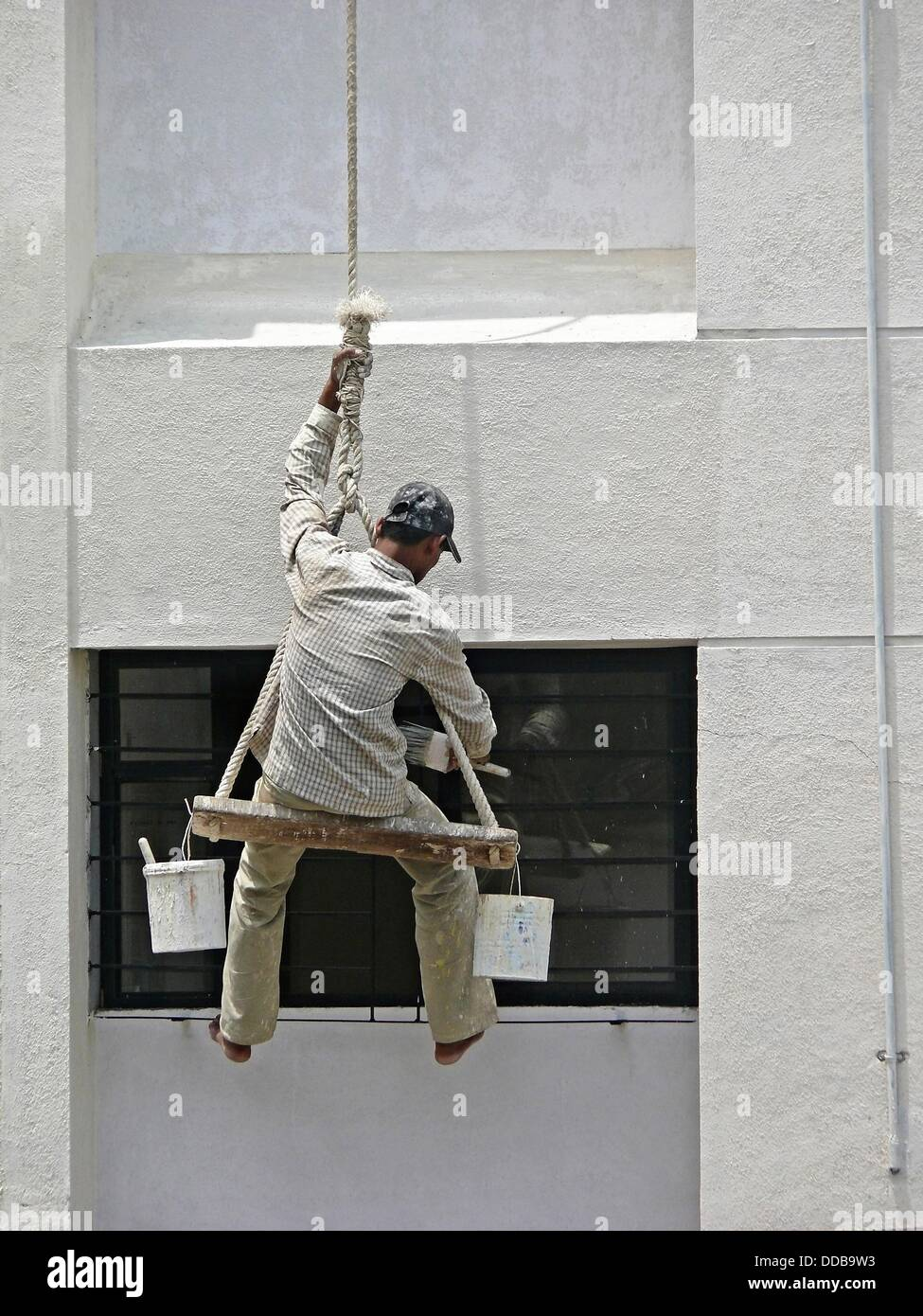 A Painter Is Seating On A Cradle For Building 180 S Exterior
