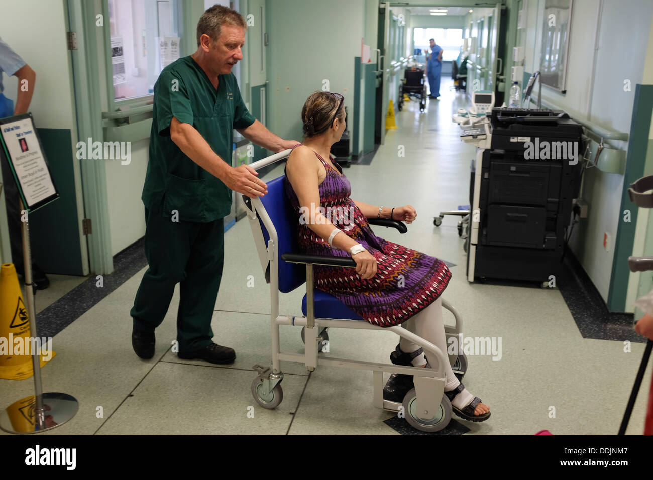 wheelchair nhs swing chair cushion covers a hospital porter helping woman being discharged from