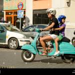Woman And Child In Traffic Riding A Classic Vespa Scooter With Civil Stock Photo Alamy