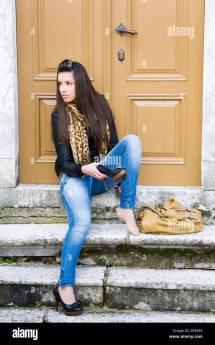 Young Woman Sitting And Removing Shoe Stock