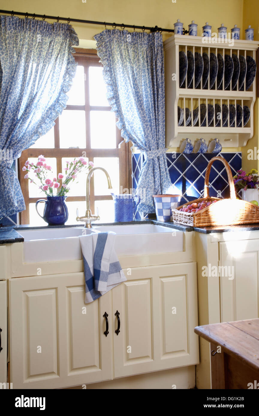 Blue Curtains On Window Above Double Belfast Sinks In Country Kitchen Stock Photo Alamy
