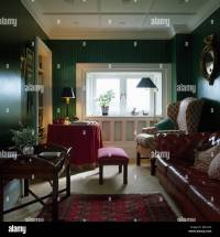 Wing chair and brown leather sofa in dark green living