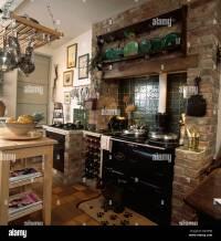 Wine storage rack beside black Aga in exposed brick ...