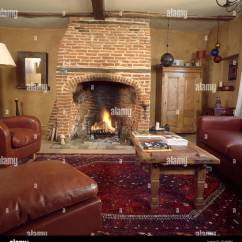 Country Living Rooms With Fireplaces Blue Couch Room Lighted Fire In Exposed Brick Fireplace Neutral Rustic Wooden Coffee Table And Brown Leather Chairs