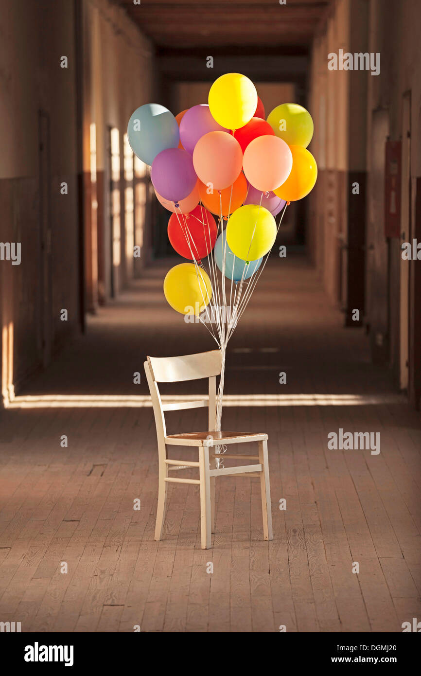 chair with balloons wooden glider cushions tied to an old standing in empty corridor building germany