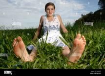 Teenage Girl Wearing Dress Sitting With Bare Feet In