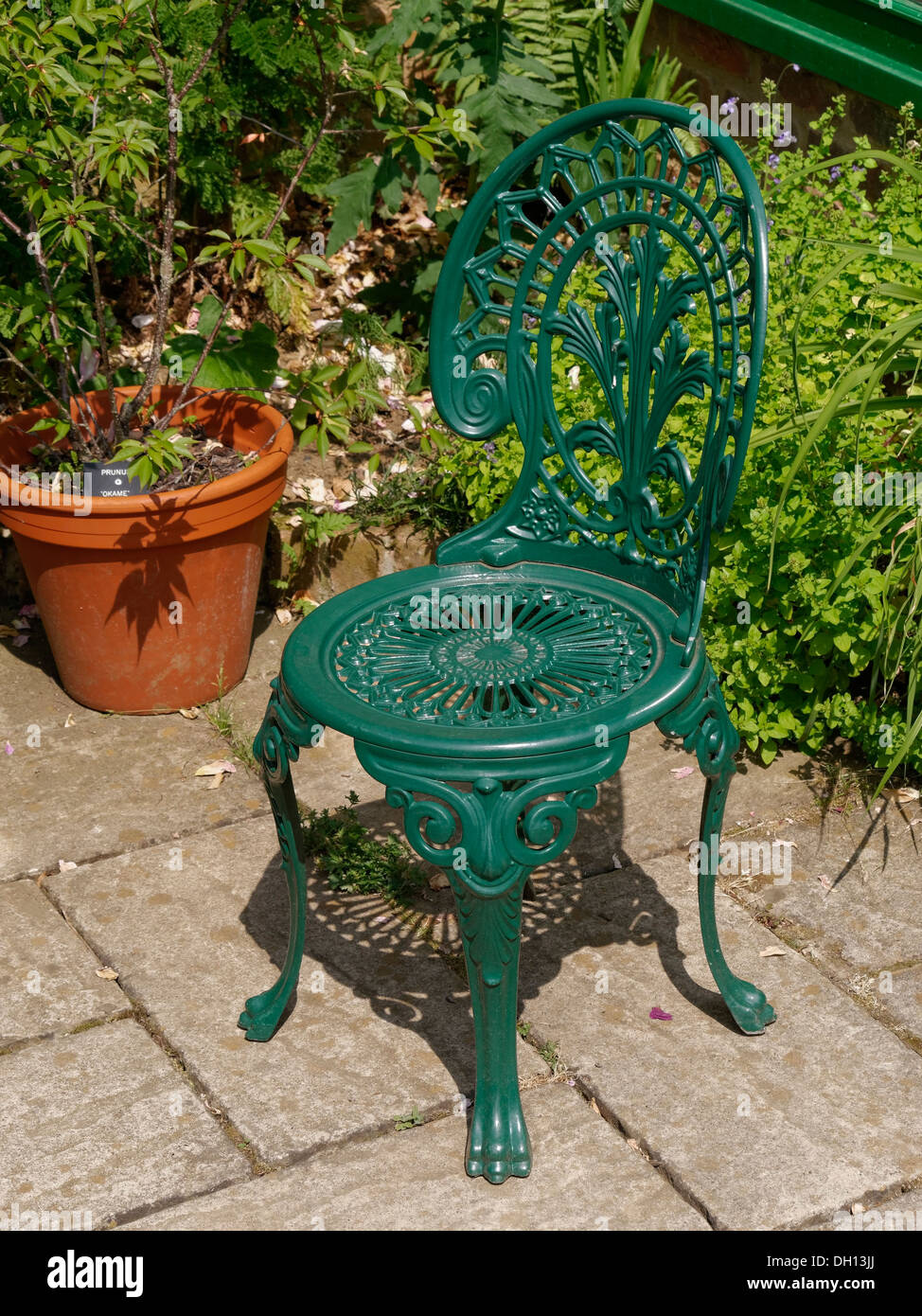 iron outdoor chairs upholstered for sale green painted ornate cast metal garden chair on slabbed patio stock barnsdale gardens oakham rutland england uk