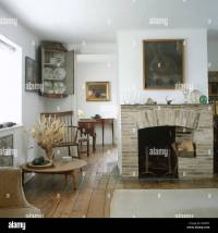 Large painting above brick fireplace in open-plan cottage ...