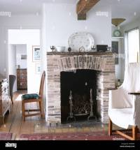 White loose cover on chair beside central fireplace with ...