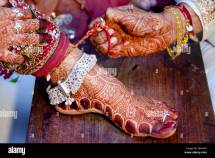 Groom Removing Thread Feet Of Bride In Indian Wedding