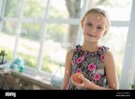 Young Girl In Floral Dress Holding Peach Fruit Stock