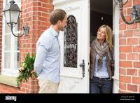Mid adult couple, woman opening front door Stock Photo