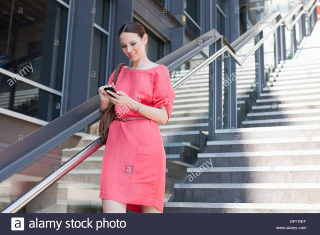 Woman Using Cell Phone On Sunny Stairs