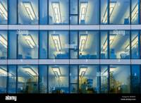 Facade of a modern office building with lights on in the ...