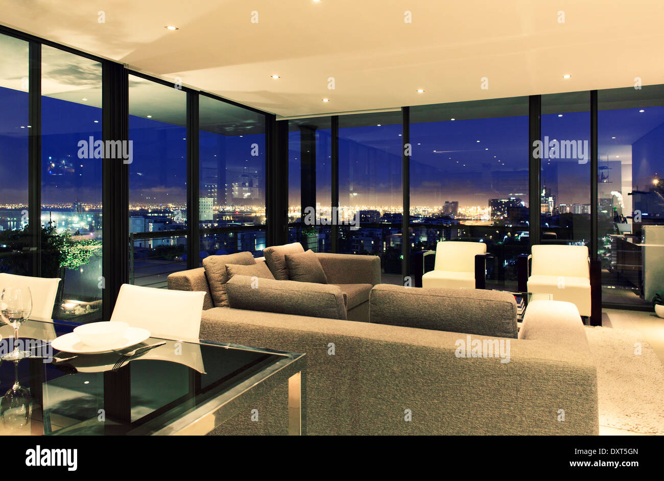 Illuminated modern living room overlooking city Stock