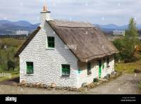 A white house with green door and trim and a thatched roof ...