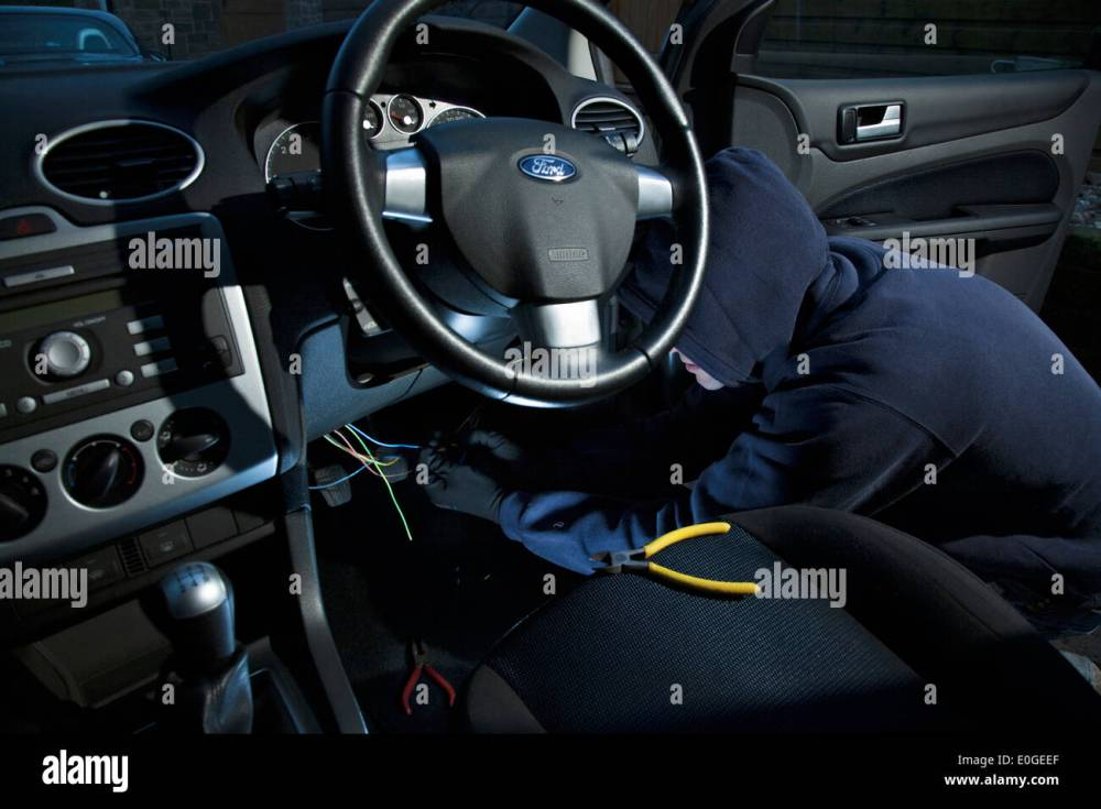 medium resolution of a man wearing a hoody hot wiring a car stock image