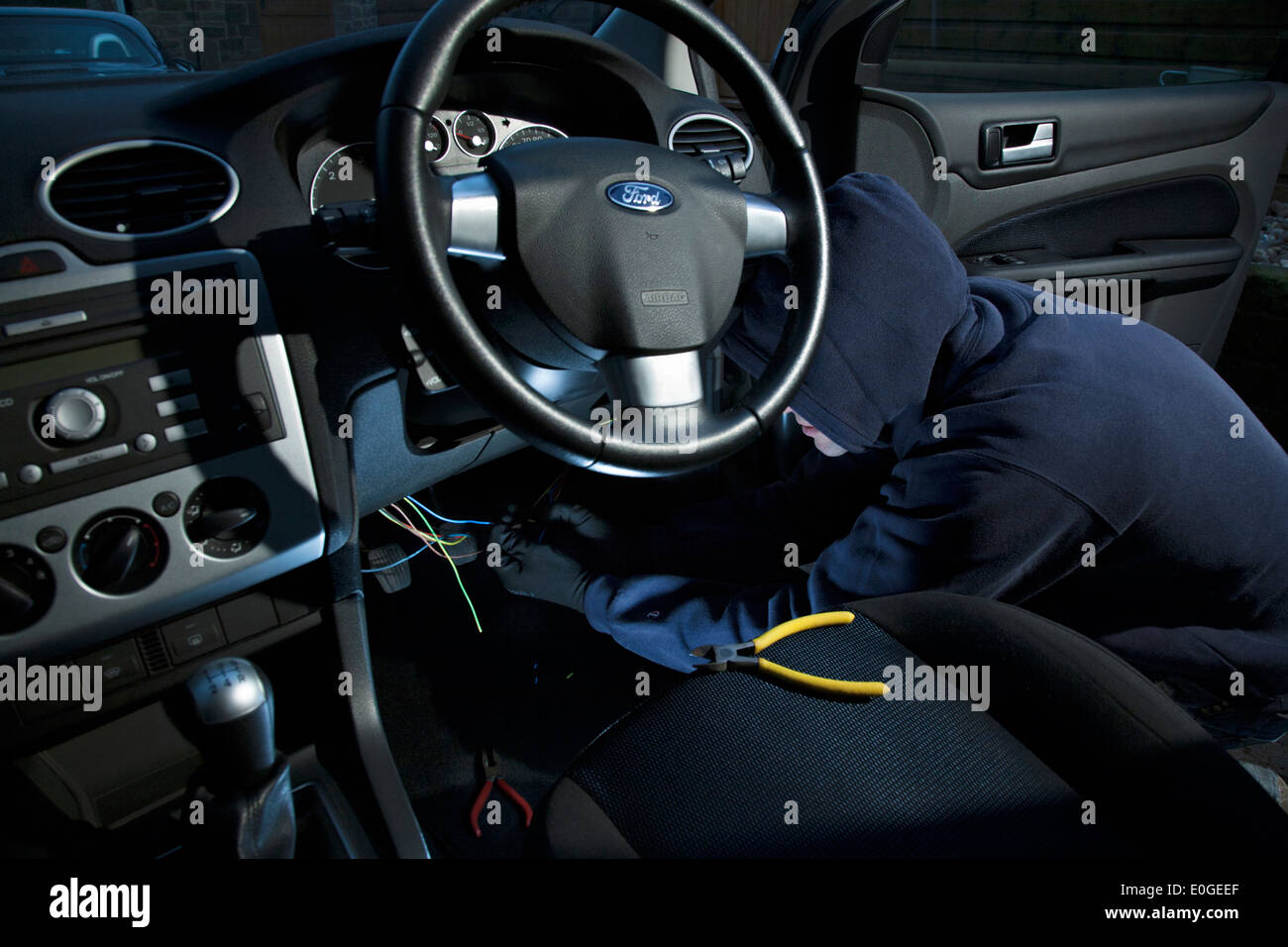 hight resolution of a man wearing a hoody hot wiring a car stock image