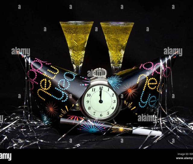 New Years Eve Party Hats Noise Maker And Streamer With Clock Showing Midnight And Two Flutes Of Champaign