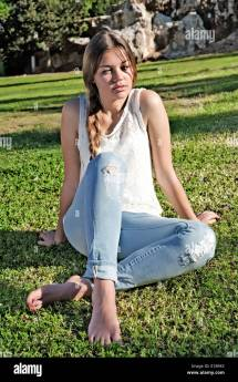 Barefoot Girl In Ripped Jeans Sitting Grass