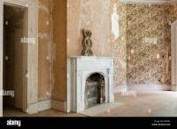 Old bricked up fireplace in empty room with peeling ...