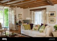 White sofa in living room with wooden ceiling beams and ...