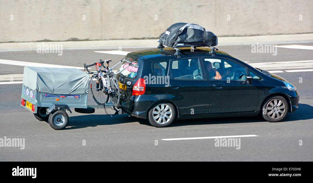 Hatchback car with roof rack cycle rack and towing trailer