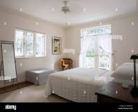 Modern white bedroom in Barbados with ceiling fan above ...