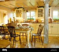Old wooden chairs at painted table in cottage kitchen with ...