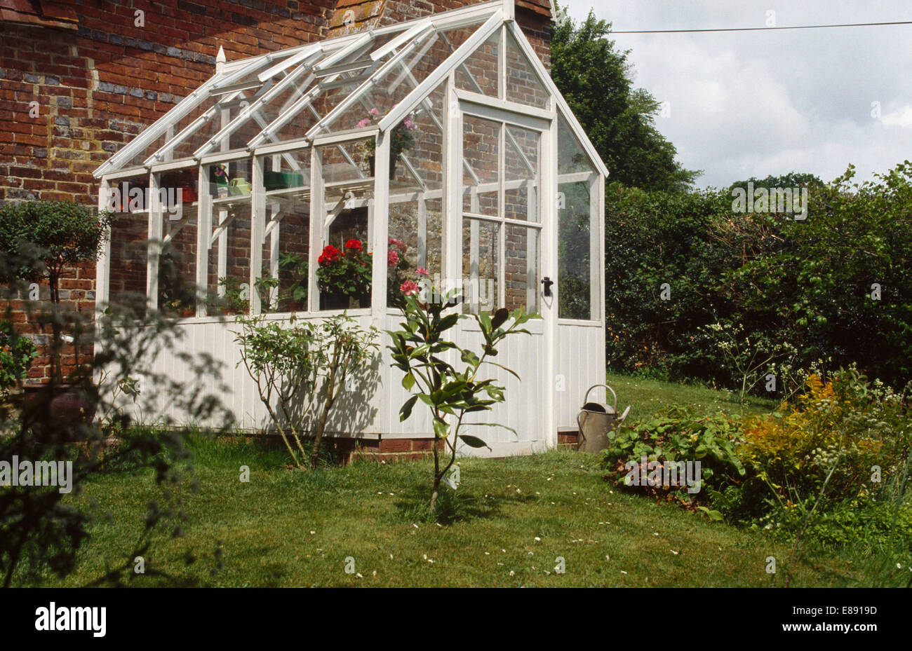 Greenhouse against brick wall of house with large garden