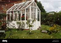 Greenhouse against brick wall of house with large garden ...