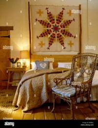Patchwork wall hanging above bed with cvream quilt in ...